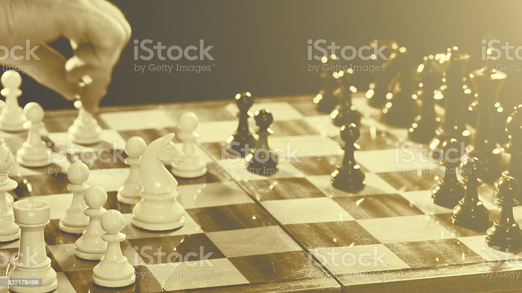Chess player's hand reaching for a chess piece stock photo