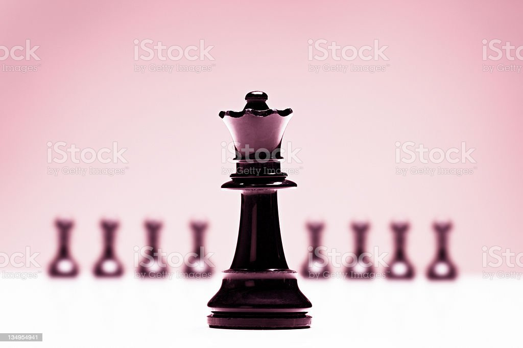 Chess queen in front of pawns on pink background stock photo
