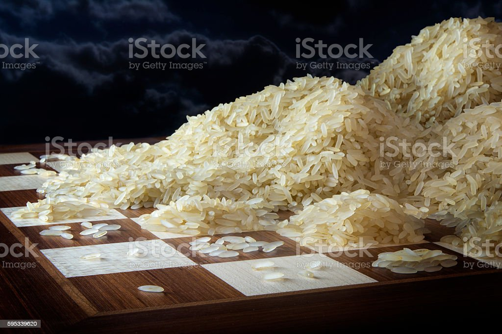 chessboard with exponential  growing heaps of rice grains stock photo