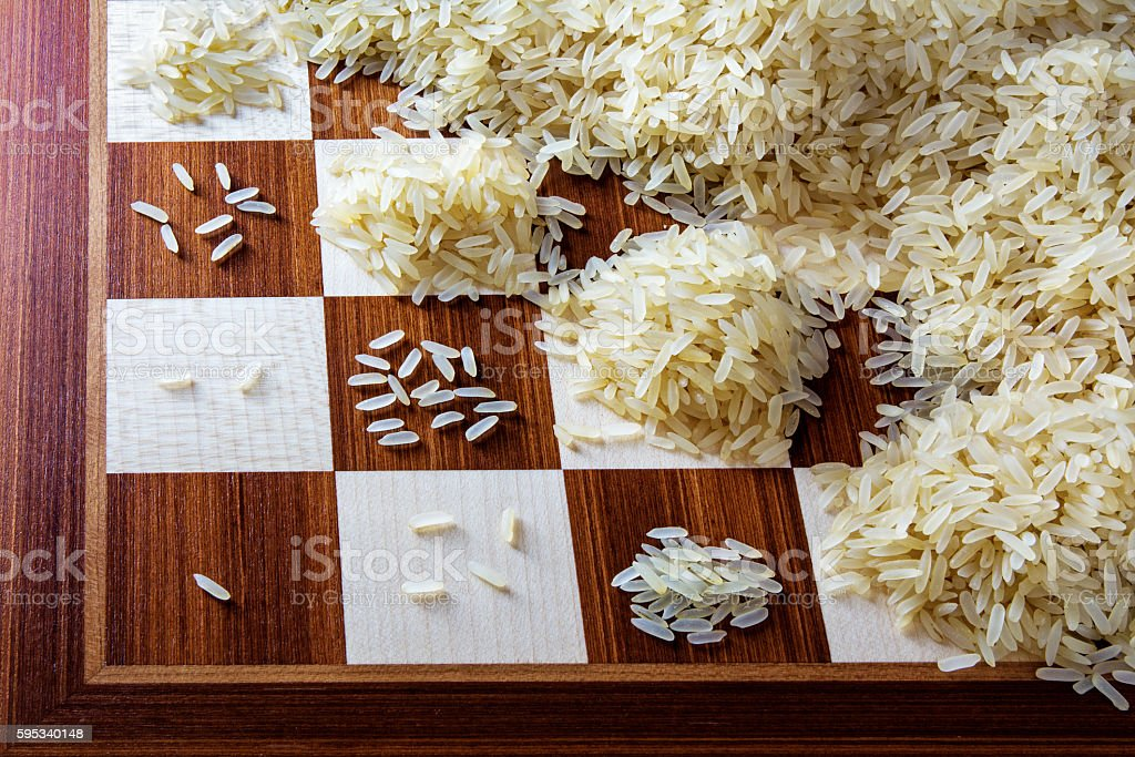 chessboard with expotential growing heaps of rice grains, concept stock photo