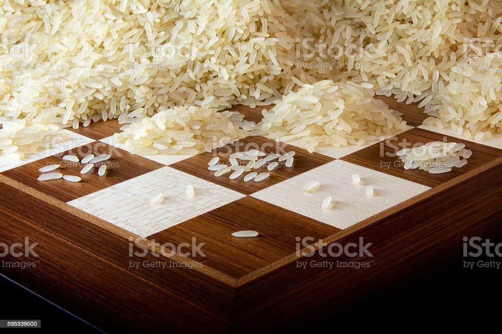 chessboard with growing heaps of rice grains stock photo