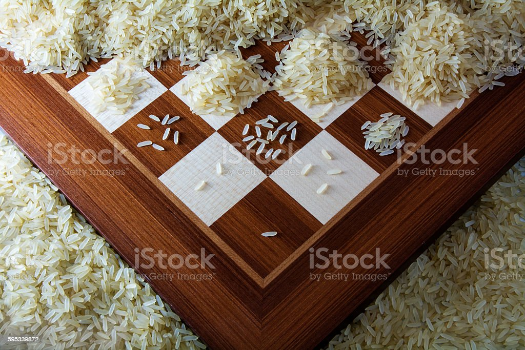 chessboard with growing heaps of rice grains, view from above stock photo