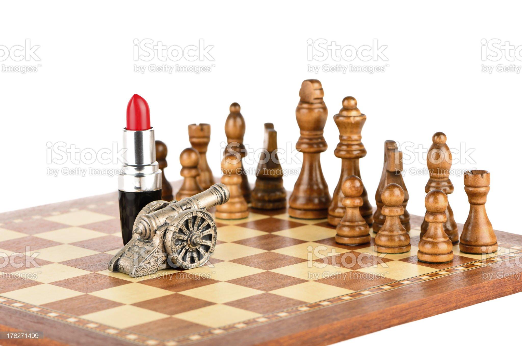 Chessmen, lipstick and a gun royalty-free stock photo