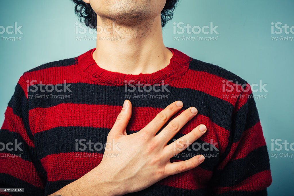 Chest view of man with hand on his heart pledging allegiance stock photo