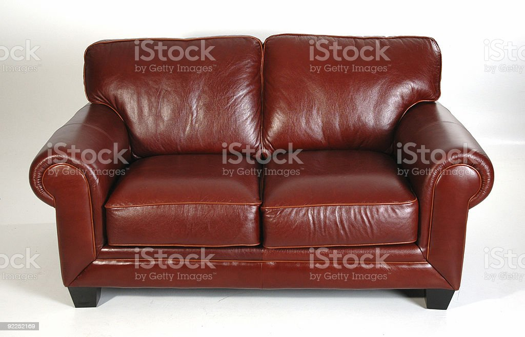 Chestnut leather love seat with rounded arms and cushions  royalty-free stock photo