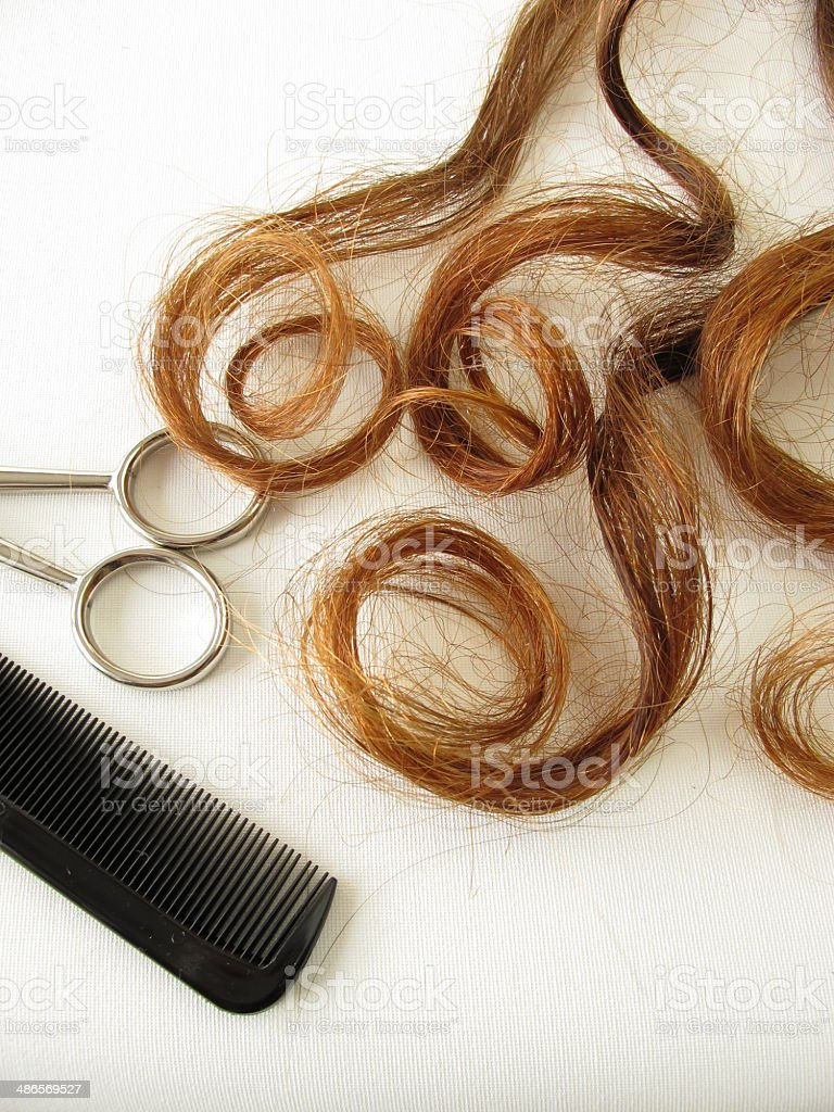 Chestnut-brown hair curls, scissors and comb stock photo