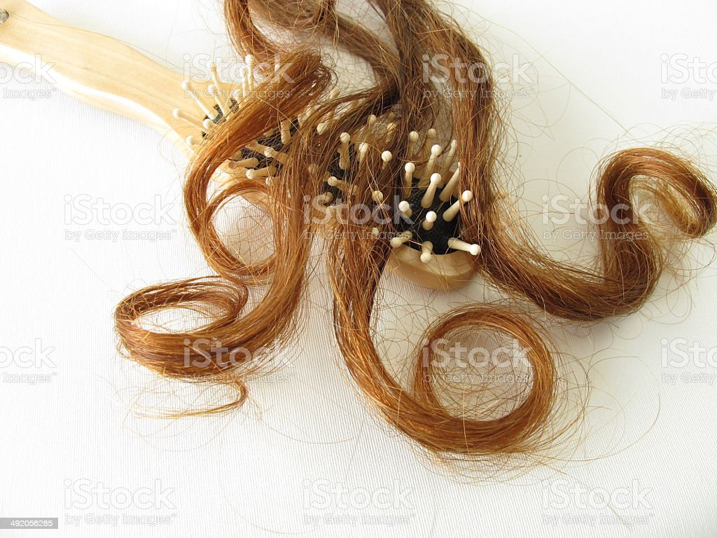 Chestnut-brown hair strand and hairbrush stock photo
