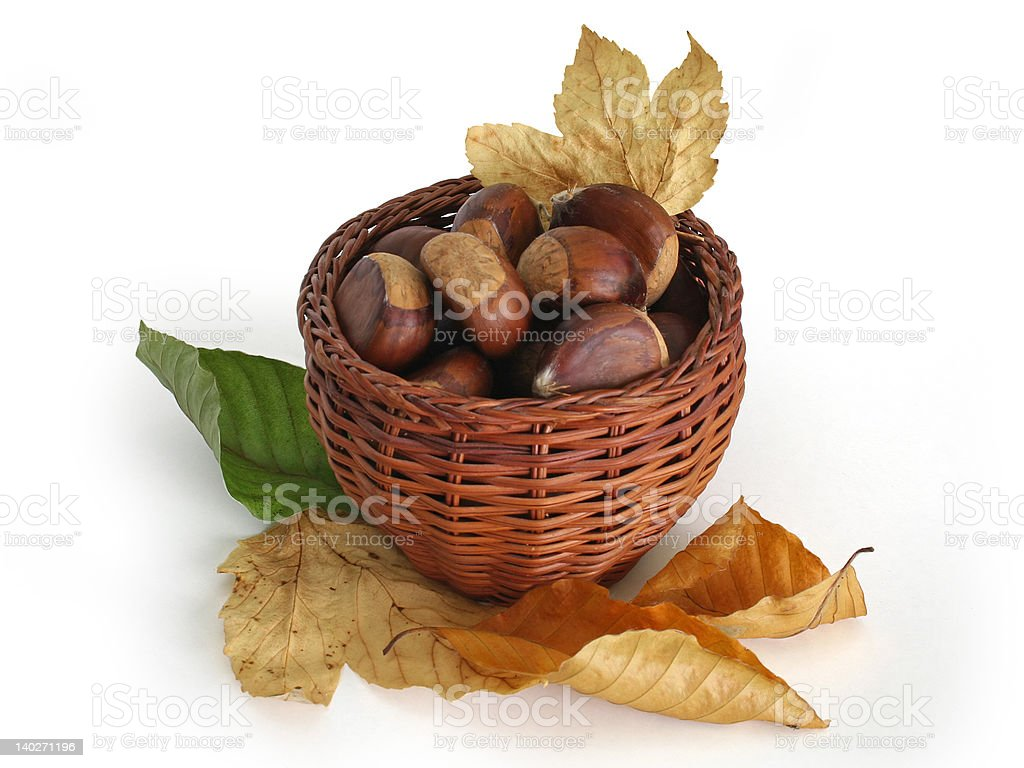 Chestnuts in a basket with autumn leaves royalty-free stock photo