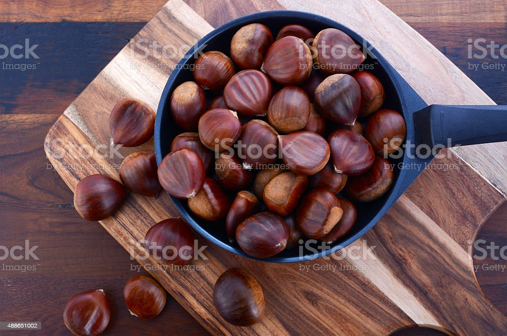 Chestnuts on Rustic Wood Table stock photo