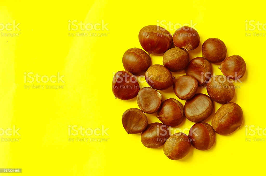 Chestnuts pattern on yellow background top view chestnut stock photo