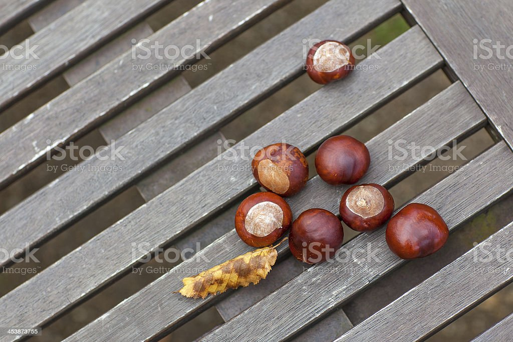 Chestnuts with leaves on wooden table royalty-free stock photo