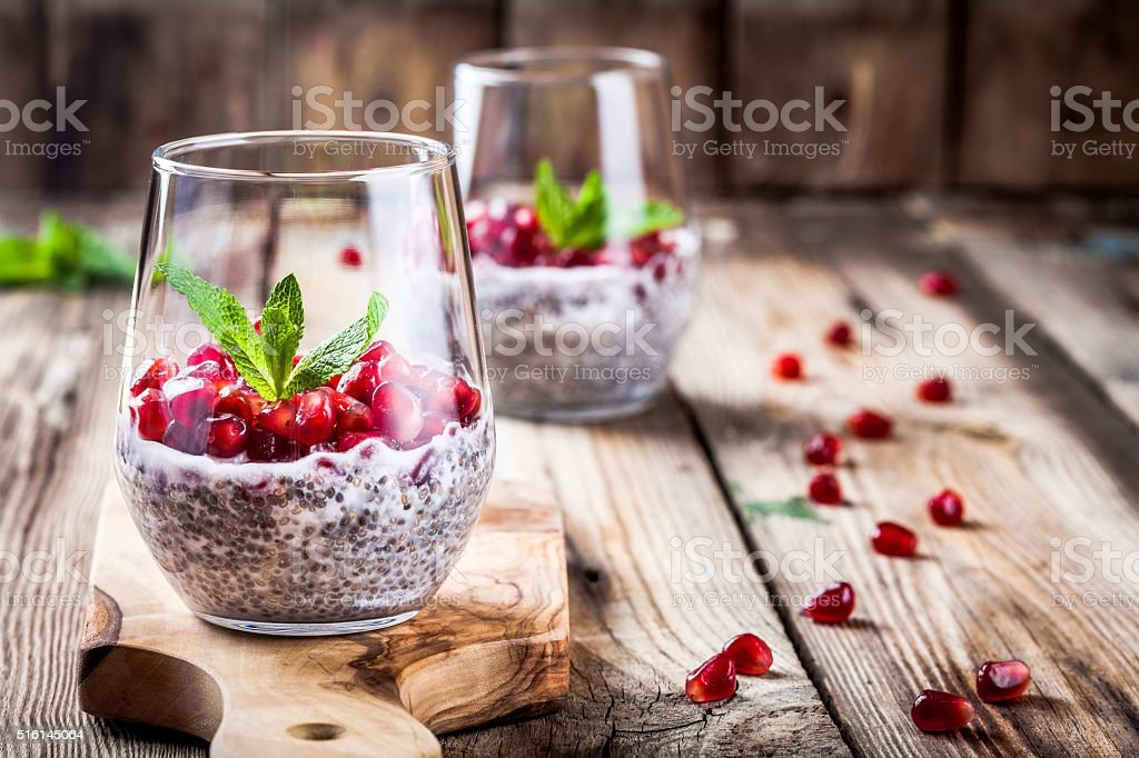 chia pudding with pomegranate seeds and mint stock photo