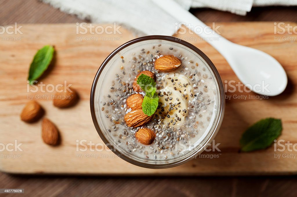 Chia seeds pudding with oat, banana and almonds with mint stock photo