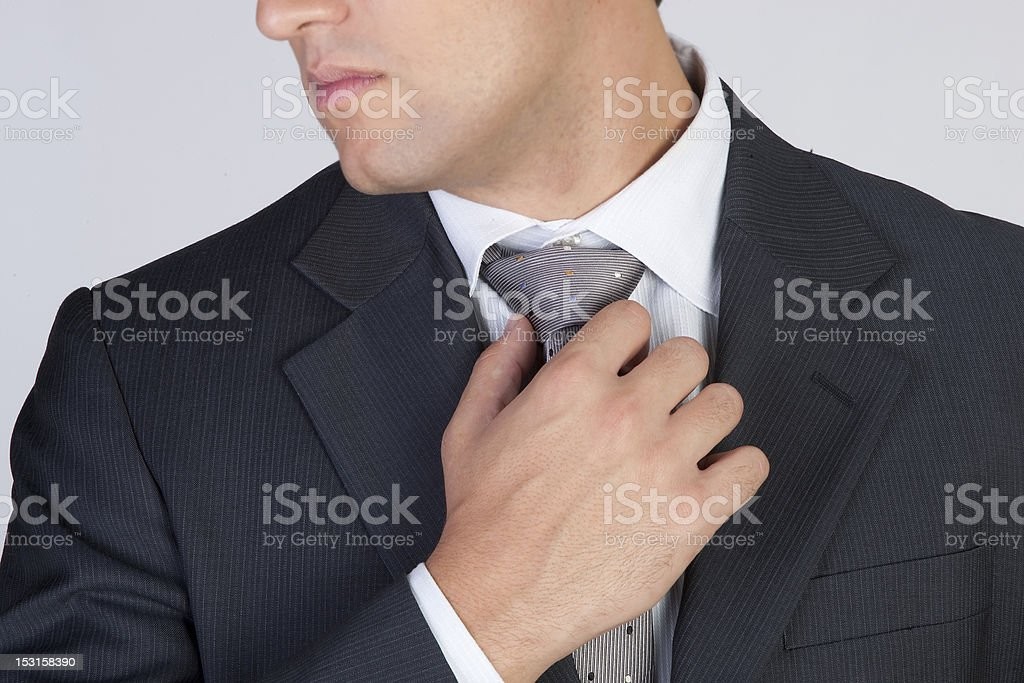 chic and stylish gentleman touching tie royalty-free stock photo