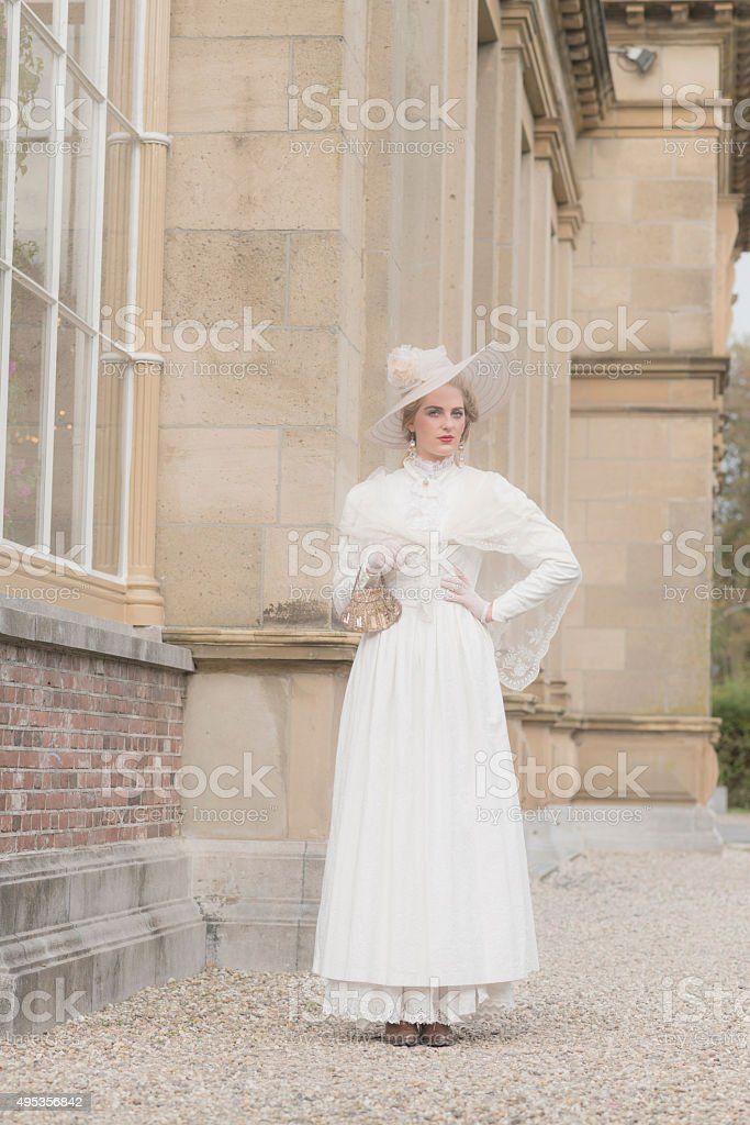 Chic victorian woman with hat walking along mansion. stock photo
