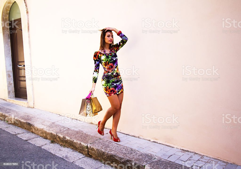 Chic Young Beauty with Shopping Bags Against Pale Wall stock photo