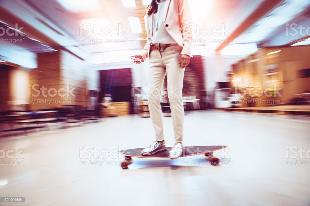 Chic young businesswoman skateboarding in offices stock photo
