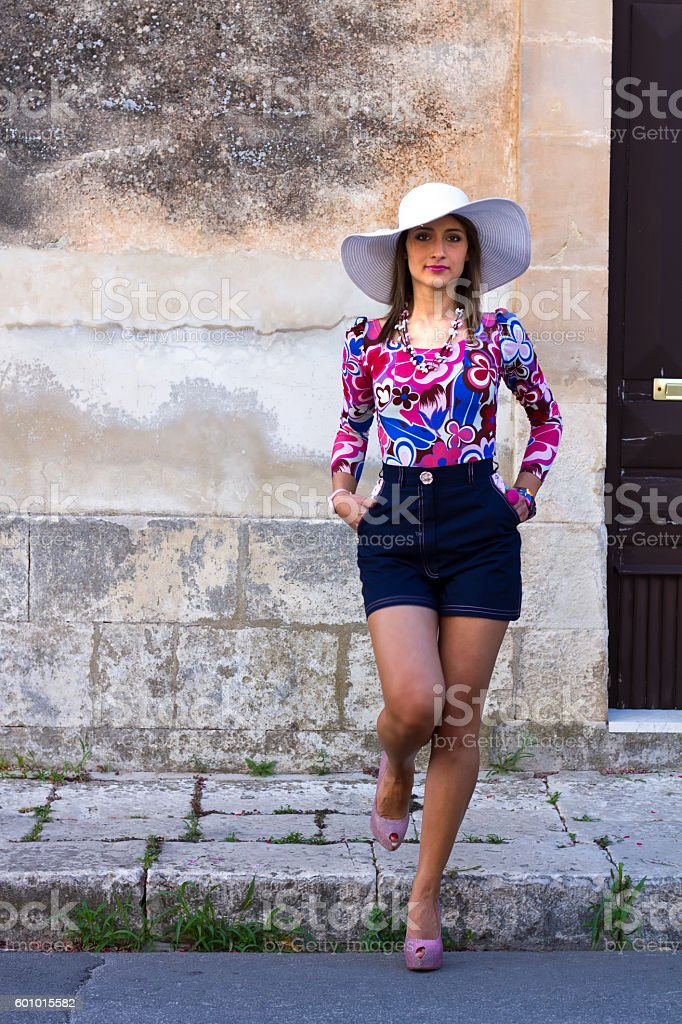 Chic Young Woman in Shorts and Sunhat, Stepping Off Curb stock photo