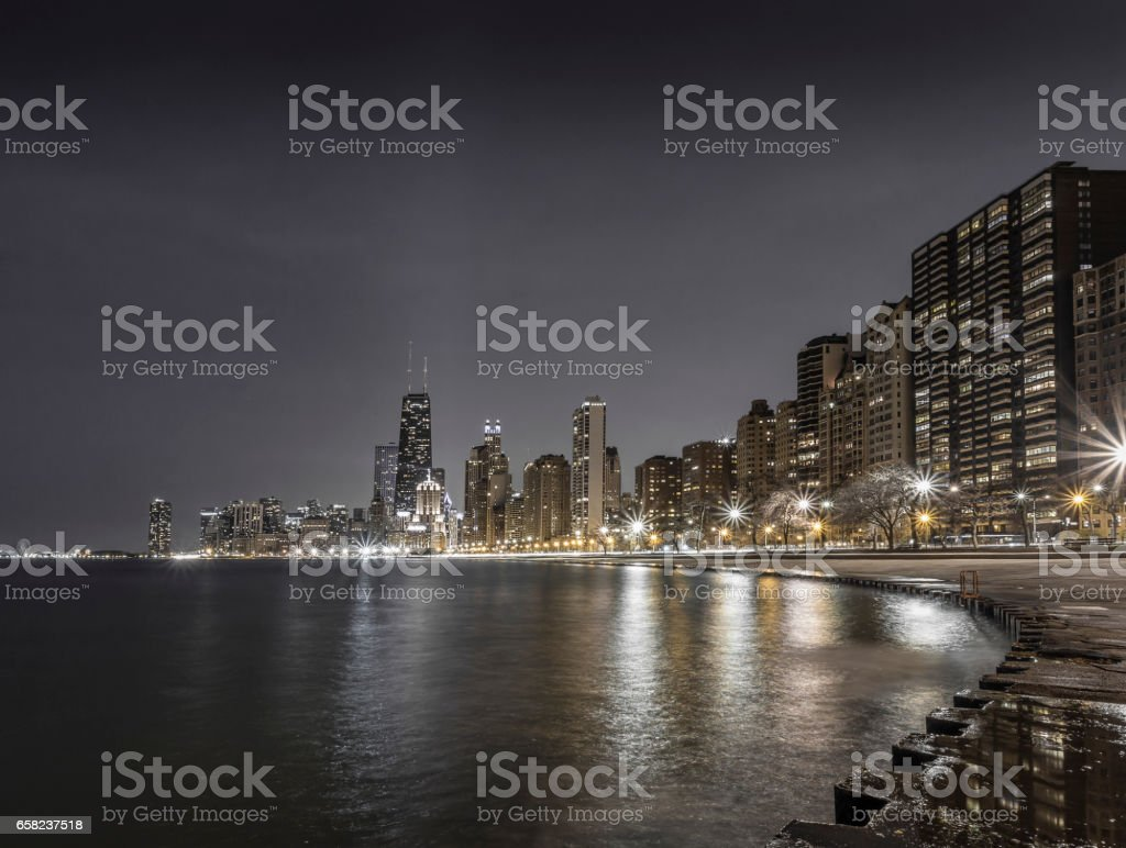 Chicago skyline at night with Lake Michigan in the foreground stock photo