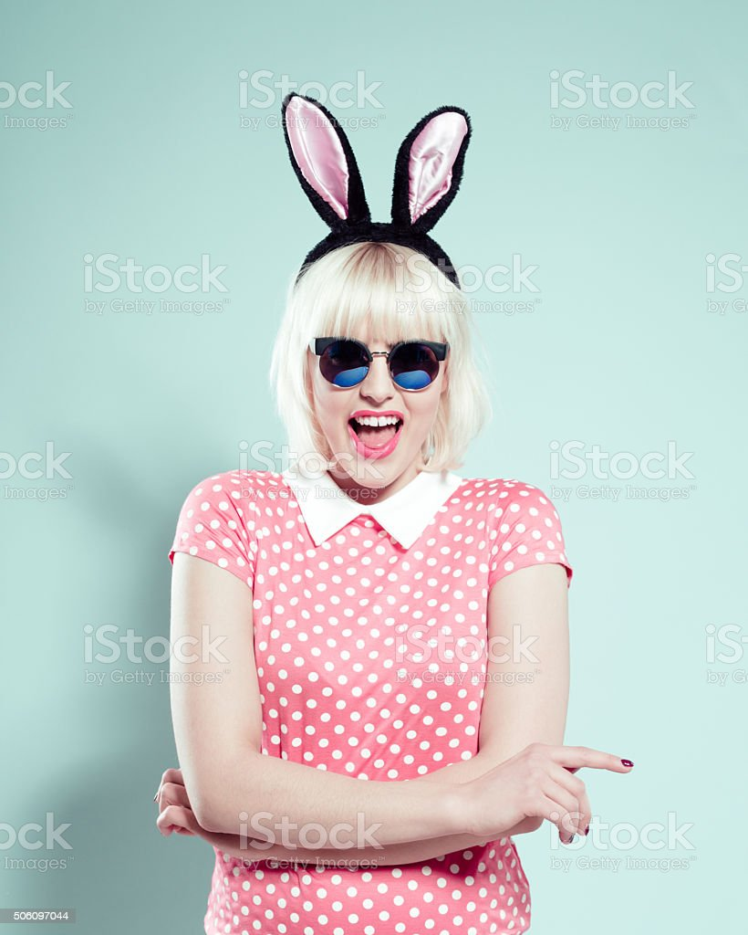 Chick blonde young woman wearing rabbit ears headband and sunglasses stock photo