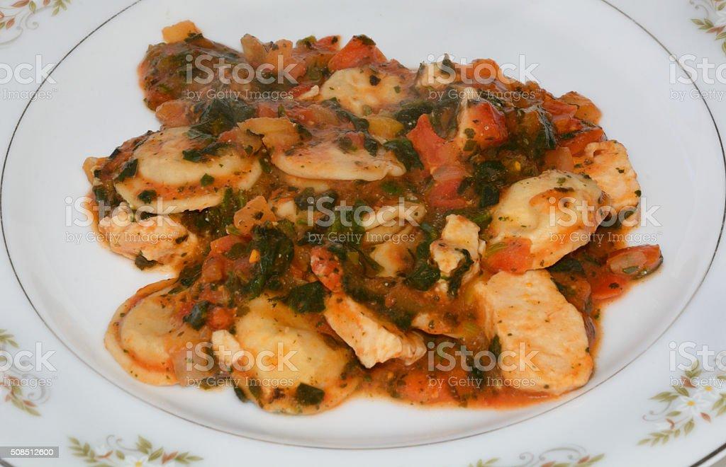 Chicken and Cheese Ravioli in spinach-marinara sauce stock photo