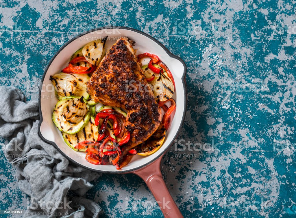 BBQ chicken and grilled vegetables in a cast iron skillet on a dark background, top view. Delicious healthy food stock photo