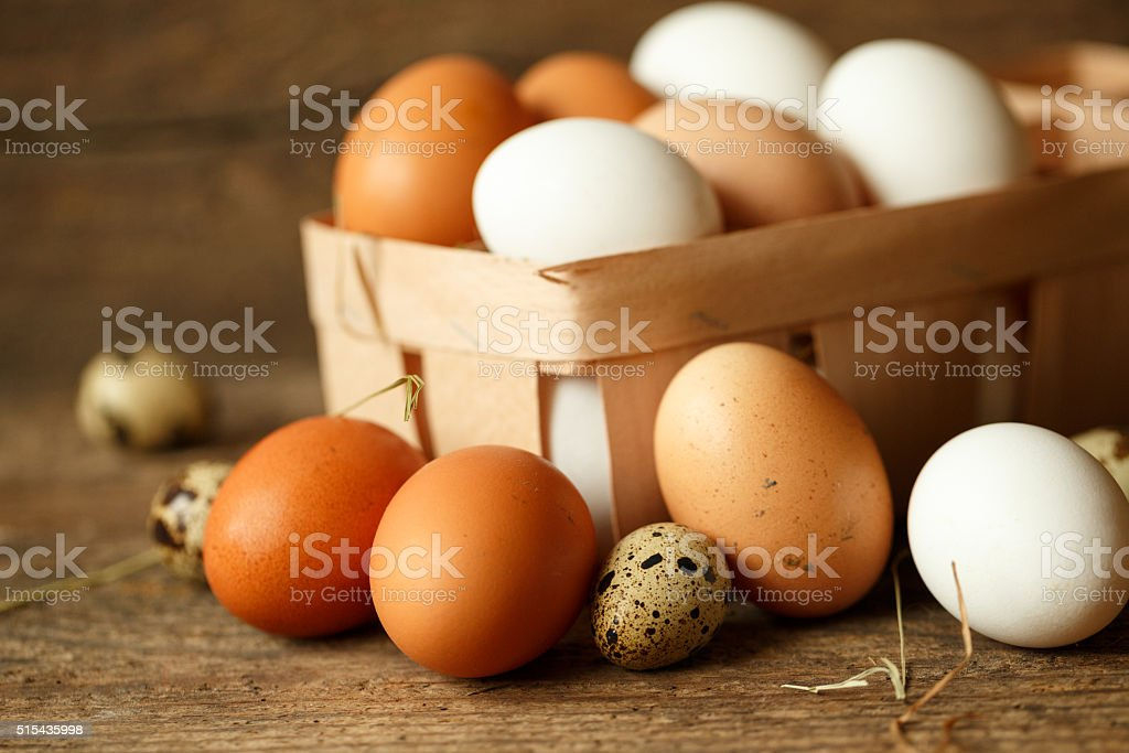 Chicken and quail eggs on a wooden rustic background stock photo
