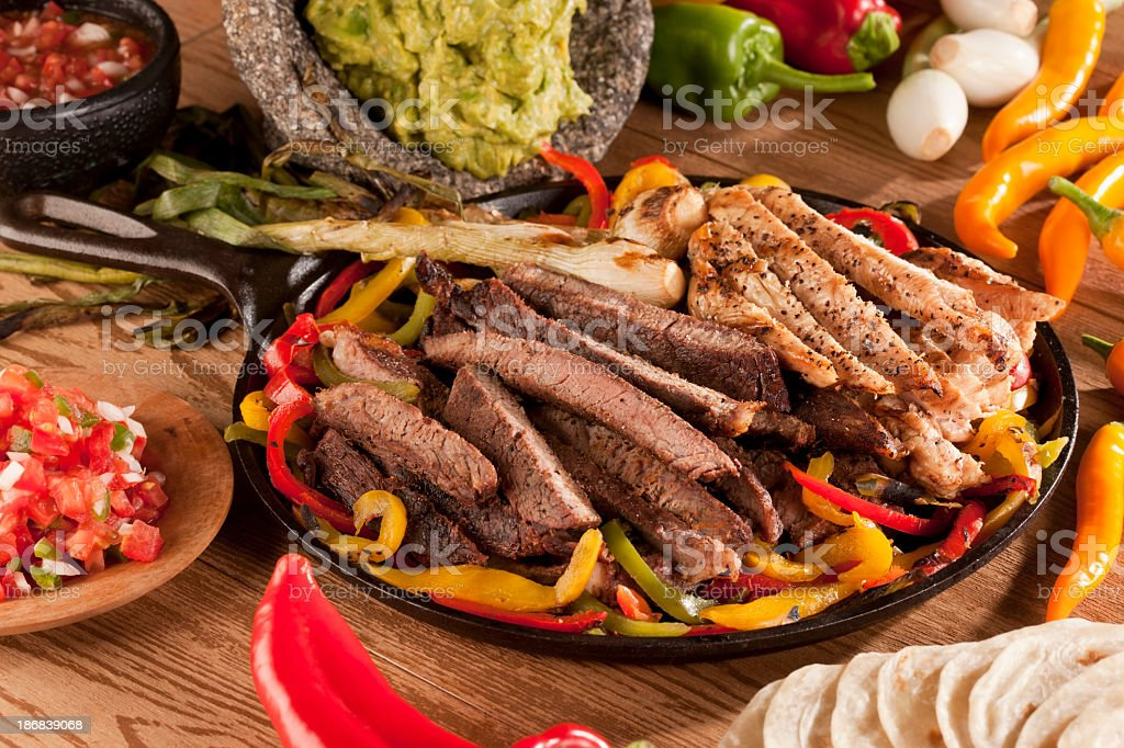 Chicken and steak fajita meat with peppers on skillet stock photo