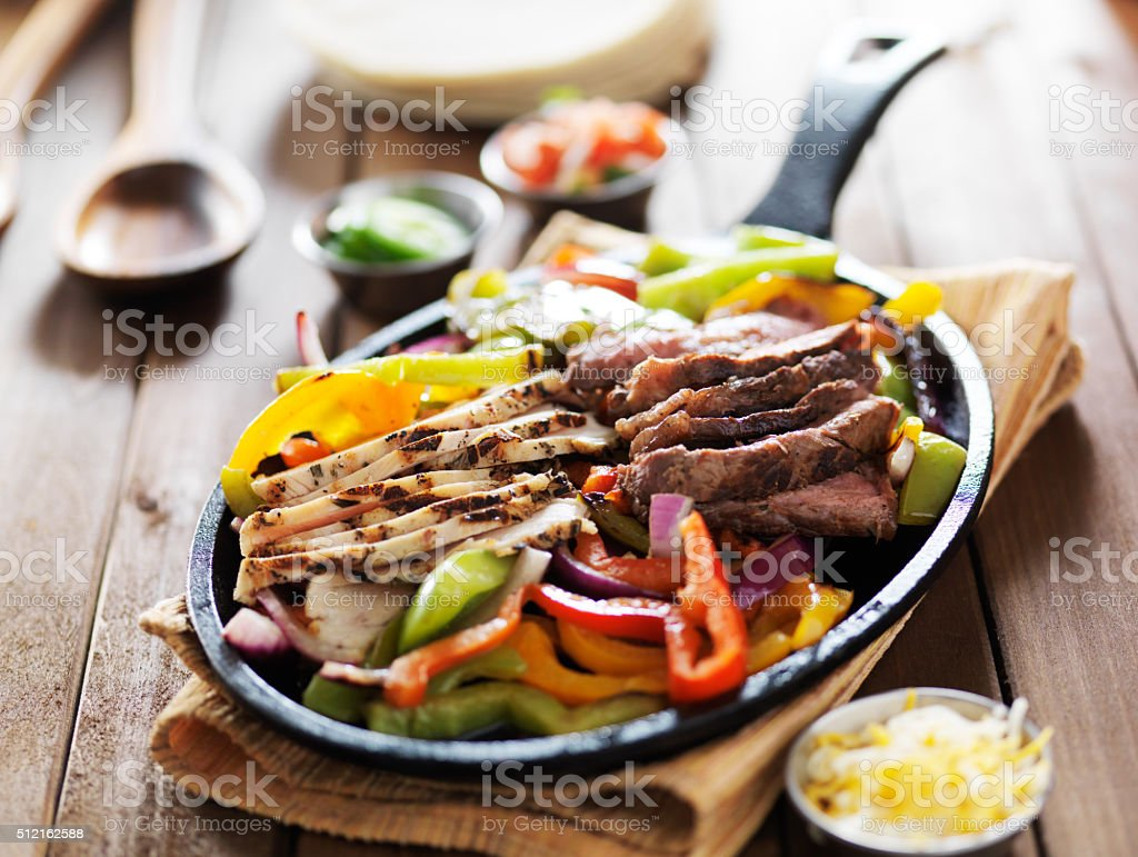 chicken and steak mexican fajitas in iron skillet stock photo