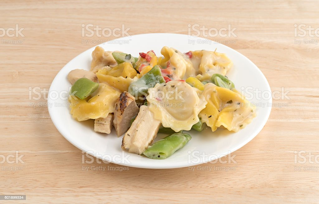 Chicken and tortellini TV dinner on a white plate stock photo