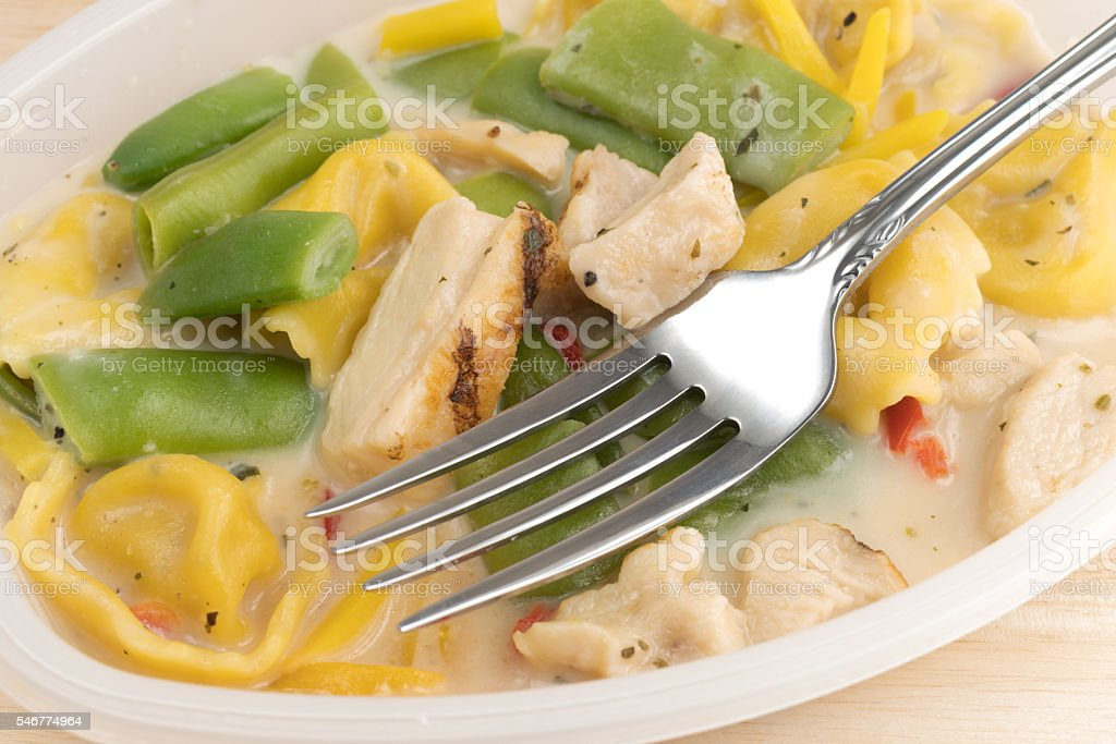 Chicken and tortellini TV dinner with a fork stock photo