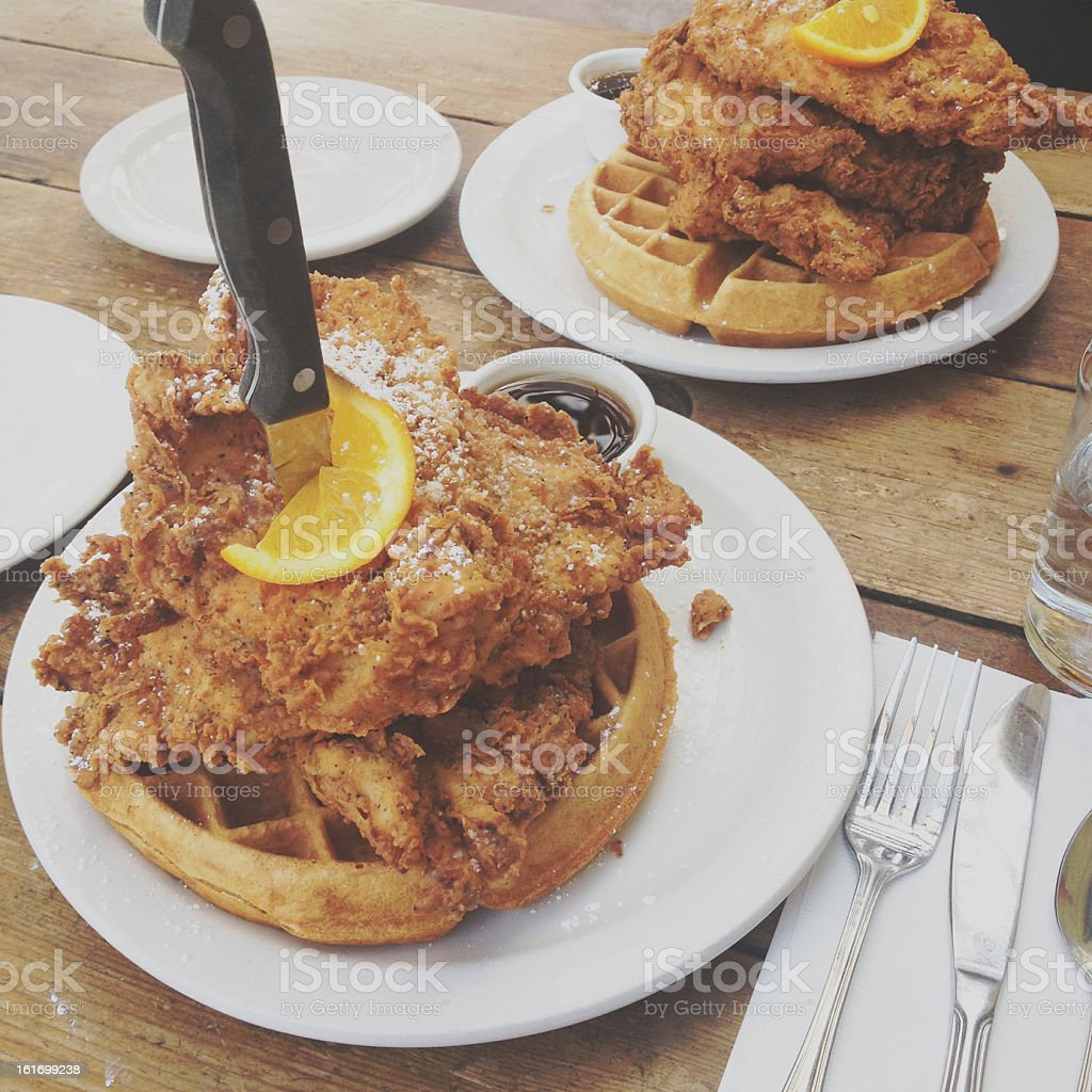 Chicken and waffles on a plate held together by a knife stock photo