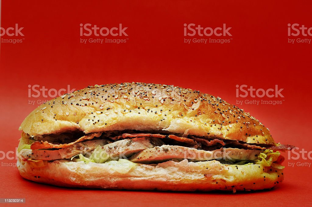 chicken bacon lettuce tomato take out sandwich against red royalty-free stock photo