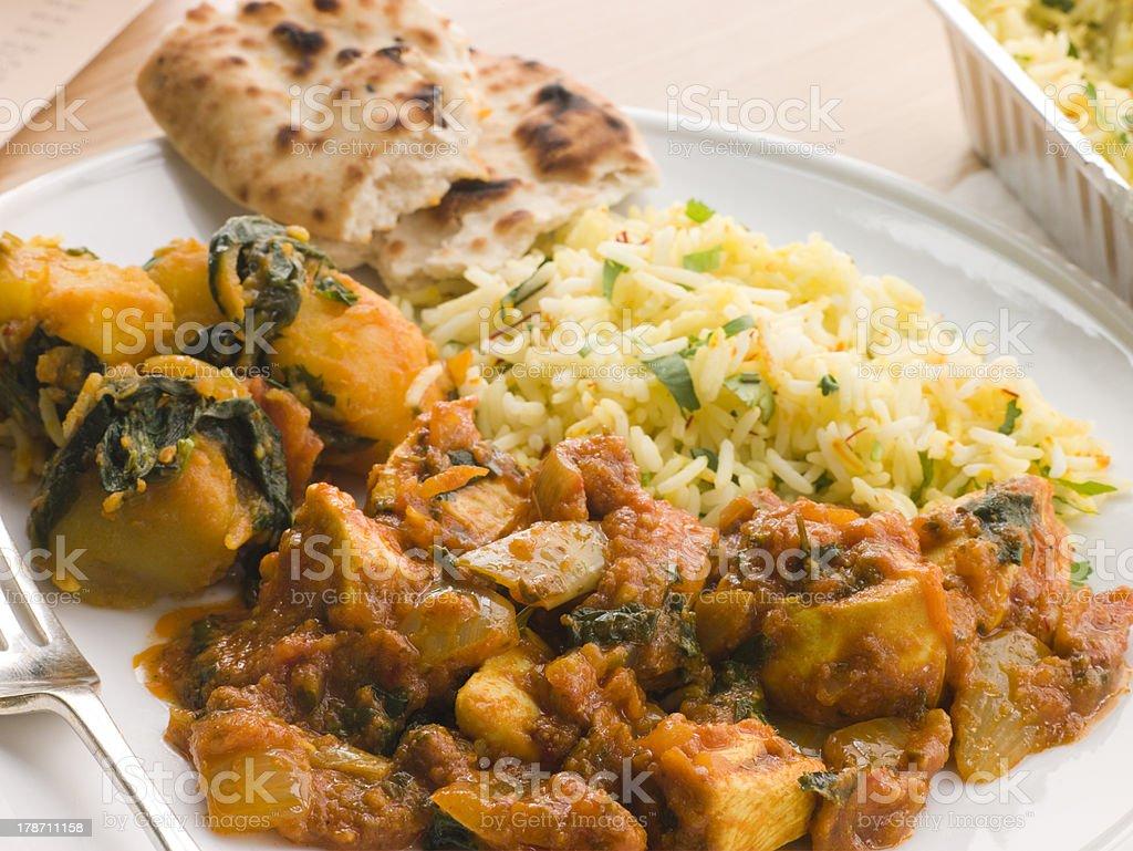 Chicken Bhoona, Sag Aloo, Pilau Rice And Naan Bread stock photo
