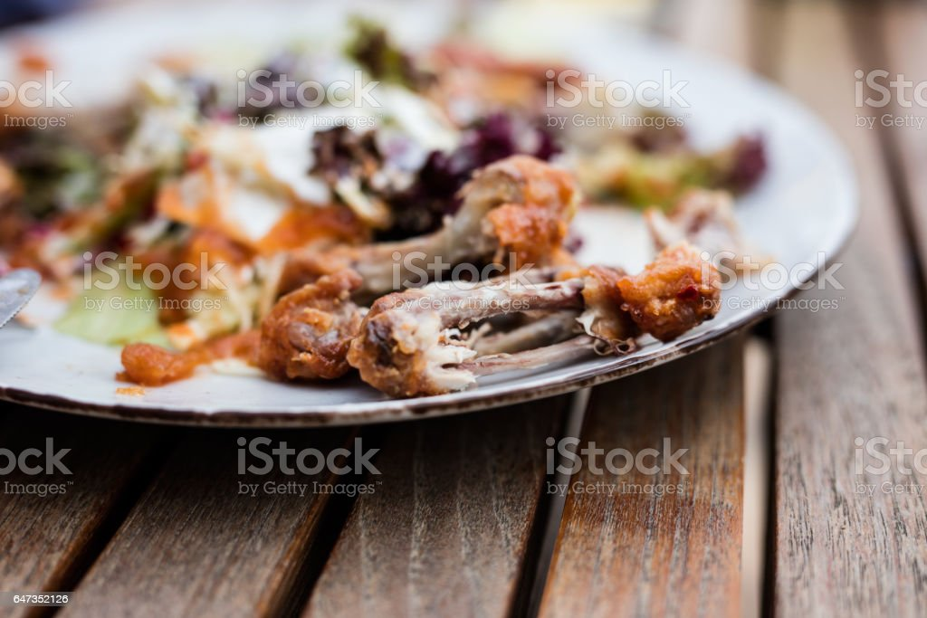 Chicken bones in white plate on wooden table, food scraps stock photo