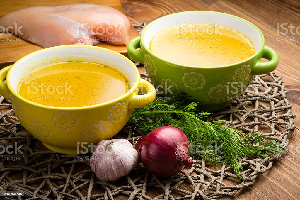Chicken bouillon in the bowls on the  wooden background. stock photo