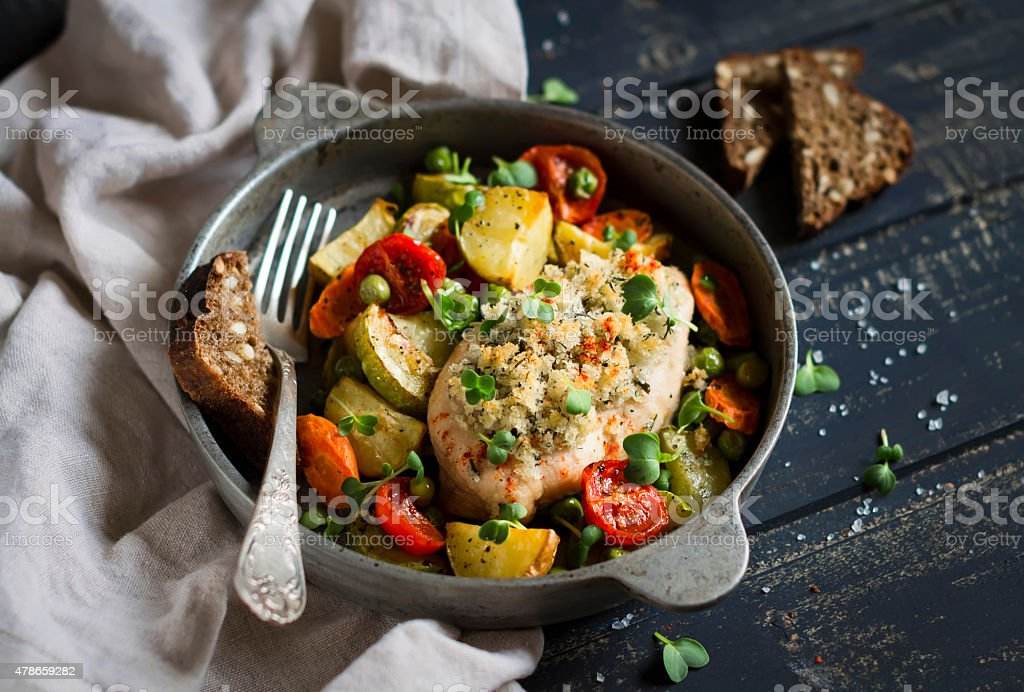 chicken breast baked with vegetables in a vintage pan stock photo