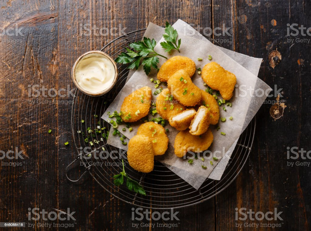 Chicken breast nuggets with tartar sauce on wire rack stock photo