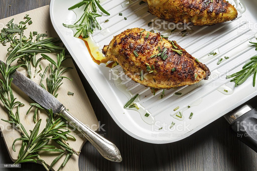 Chicken breasts in a pan with rosemary royalty-free stock photo