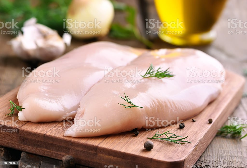 Chicken breasts on cutting board stock photo