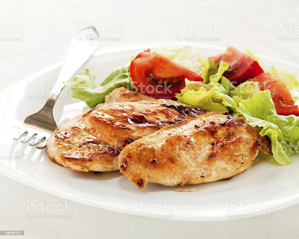 Chicken breasts with salad on plate stock photo