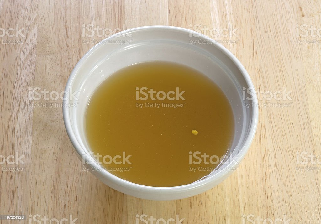 Chicken broth in bowl on table stock photo