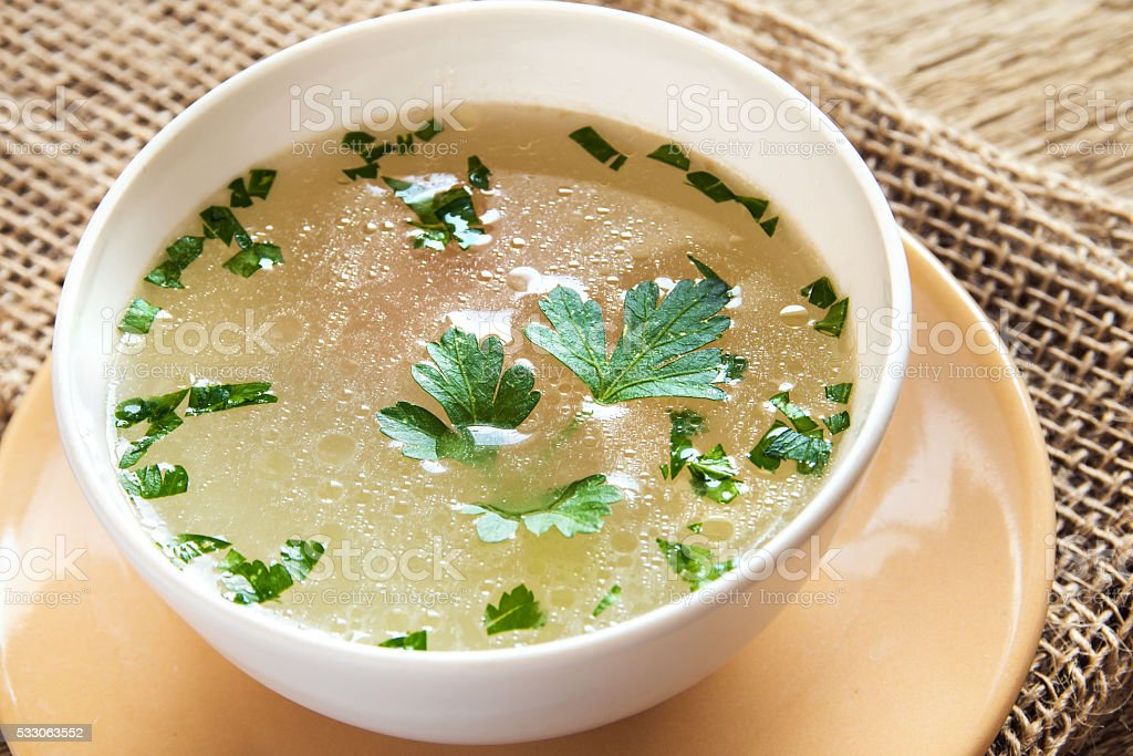 Chicken broth with parsley stock photo