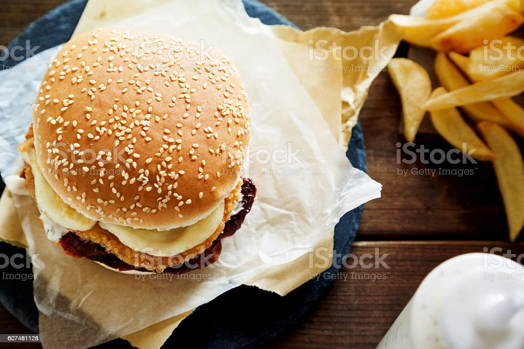 Chicken burger with melted cheese,herb sauce and French Fries stock photo