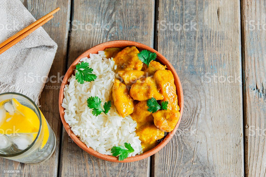 chicken curry with rice on a wooden surface stock photo