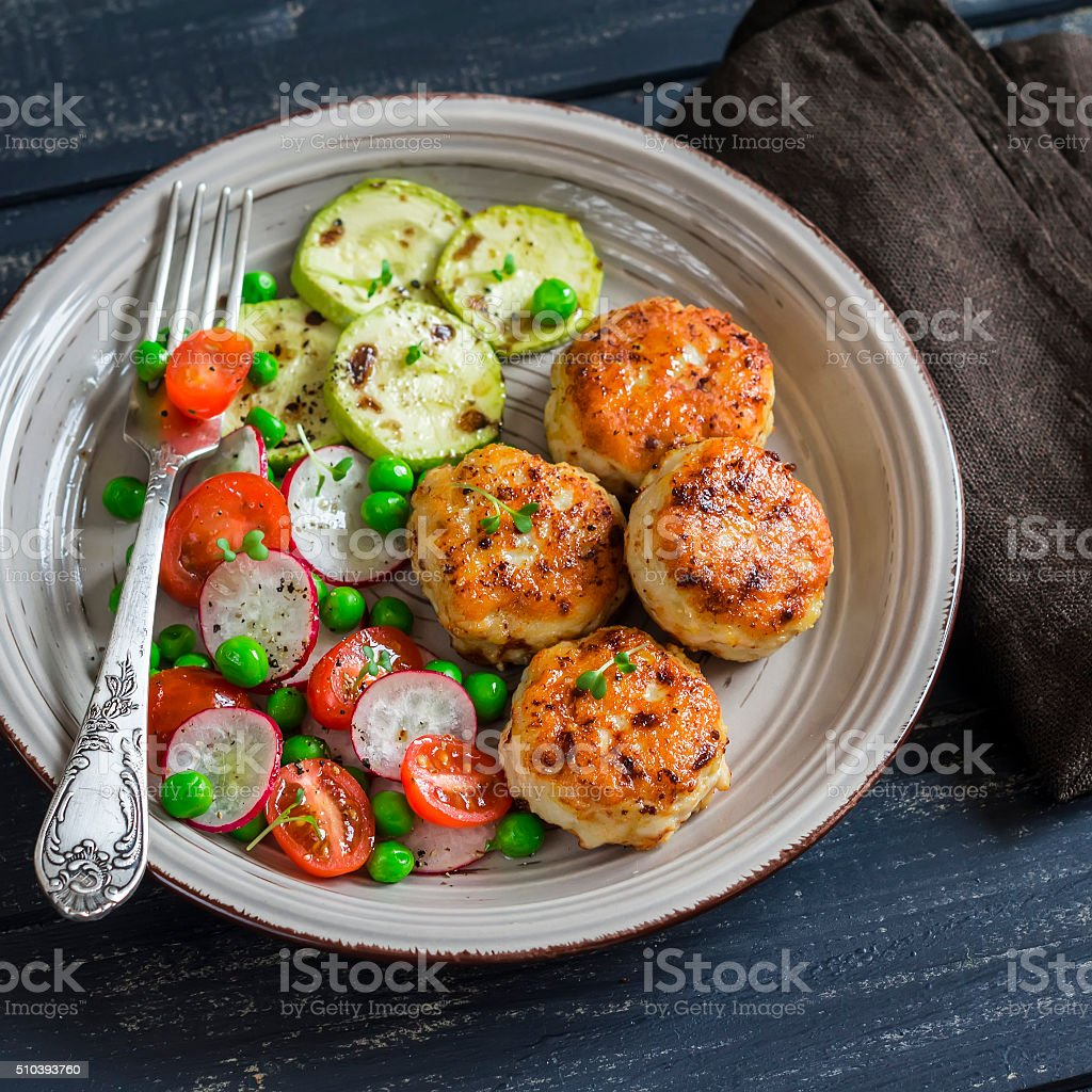 Chicken cutlets,  grilled zucchini  and fresh vegetable salad stock photo