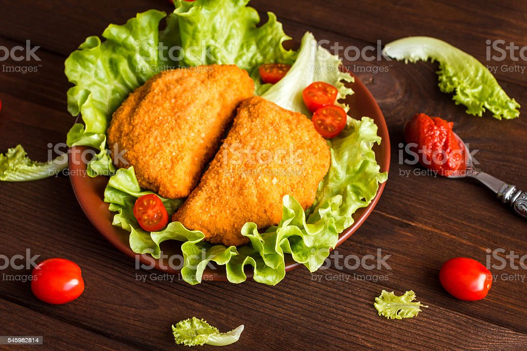 chicken cutlets with cherry tomatoes and lettuce stock photo
