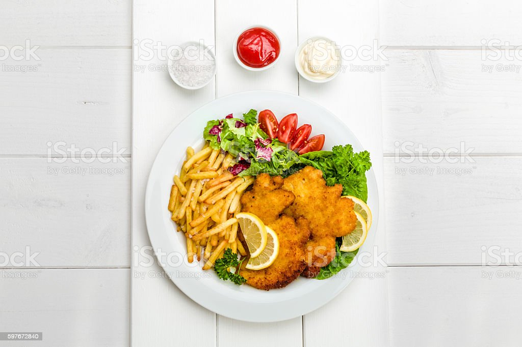 Chicken cutlets with fries and salad stock photo