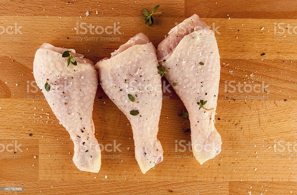 Chicken drumsticks with herbs on wooden board stock photo