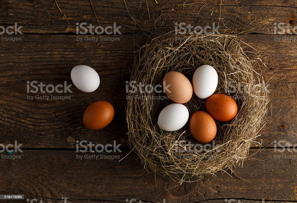 Chicken eggs in a nest on a wooden rustic background stock photo
